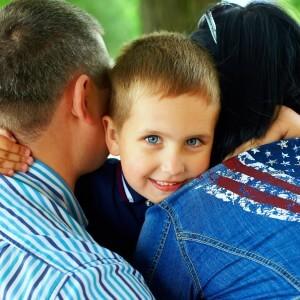 happy boy hugging parents