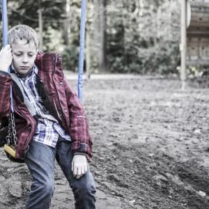 Sad or depressed boy sitting in playground swing